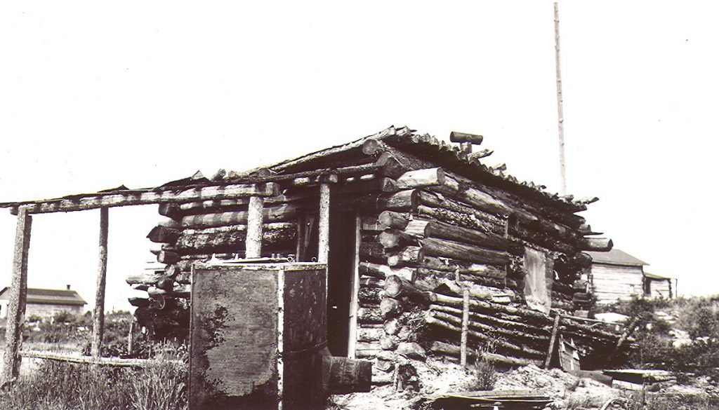 A black and white photograph of a rudimentary log cabin that is collapsing. In the background, other buildings that are similar, but in better condition.