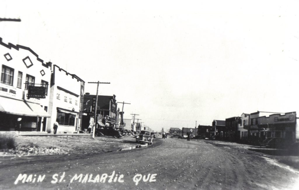Black and white photograph of a wide gravel road lined with good-quality buildings. On the left, the sign for Cleman's store and a hotel. Several cars are parked on either side. In the background, the headframe of a mine shaft.
