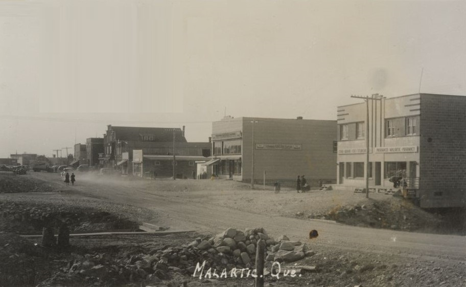 Black and white photograph of a gravel road under construction with a row of recently-constructed buildings in the background. Two women walking behind a car that raises a cloud of dust. In the foreground, a bridge and a small pile of rocks. The photograph bears the inscription