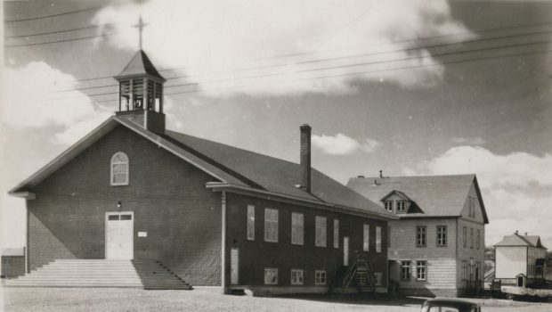 Black and white photograph of a church covered with tar paper, the cross on its bell tower merging with the clouds. At the back, a three-story plank presbytery.