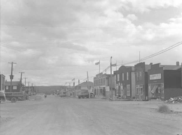 Black and white photograph of a gravel road lined with recently-constructed buildings, many with Boomtown façades. A St-Onge company truck is parked on the right.
