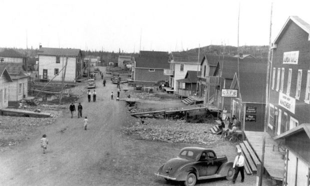 Black and white photograph of a narrow gravel road lined with rudimentary buildings. Several cars are parked and ten or so people are out and about on the public road. Long boardwalks provide access to some residences.
