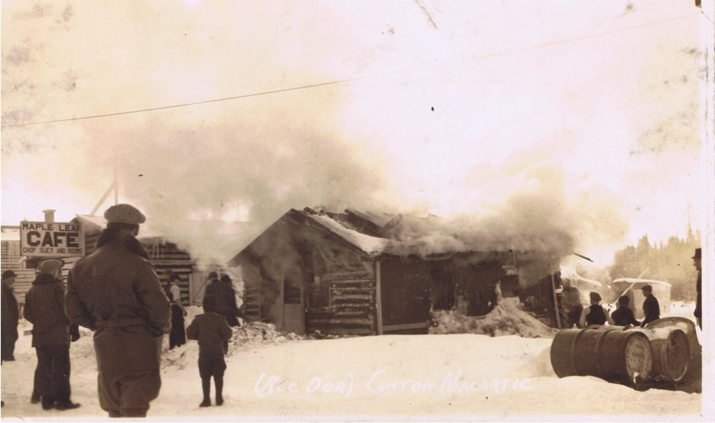 Sepia photograph of a log cabin set on fire. A large cloud of smoke fills the upper half of the photograph. A dozen curious onlookers attend the scene. On the left is a sign,