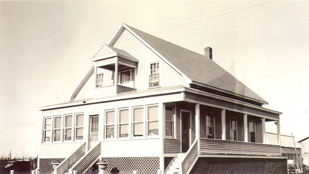 Sepia photograph of a beautiful two-storey residence. There are many windows in the front and a veranda on the right. A small balcony upstairs. In the background, a stable and a garage.