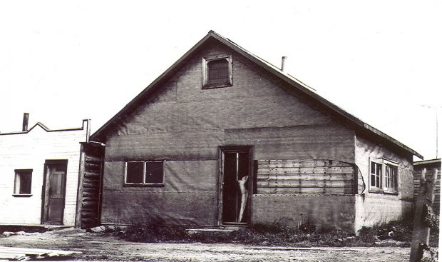 Black and white photograph of a building covered with tar paper, part of which is torn off. Four windows, two on the right side and two in front, are visible. A log cabin with a Boomtown façade on the left.