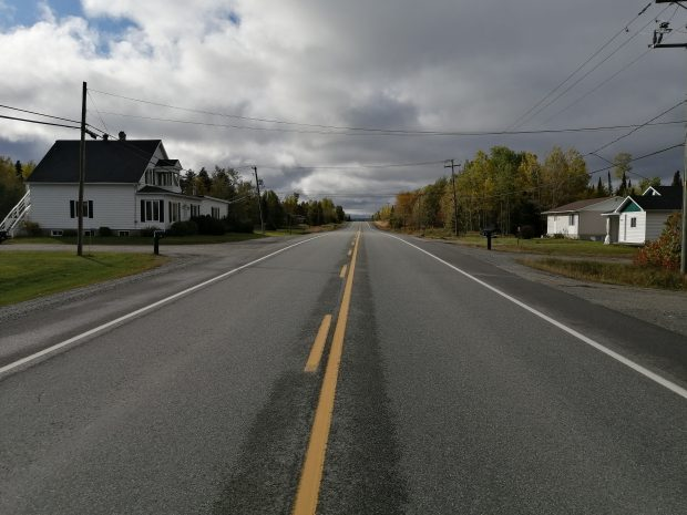 Colour photograph of an asphalt road with some residences on either side. A two-storey white house on the left and two residences on the right. The sky is cloudy.