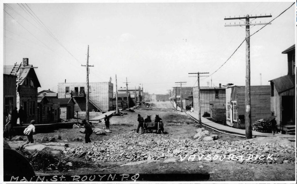 Photographie en noir et blanc d'une rue bordée de bâtiments rudimentaires et de poteaux de lignes de distribution d'électricité. Six hommes, ainsi que deux chevaux, travaillent au pavage. Des trottoirs de bois longent la rue.