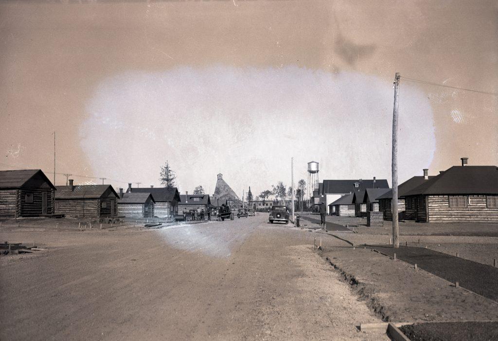 Photographie en noir et blanc d'une rue bordée de cabanes en bois rond. Des hommes travaillent à la construction des trottoirs. En arrière-plan, un château d'eau et un chevalement minier.