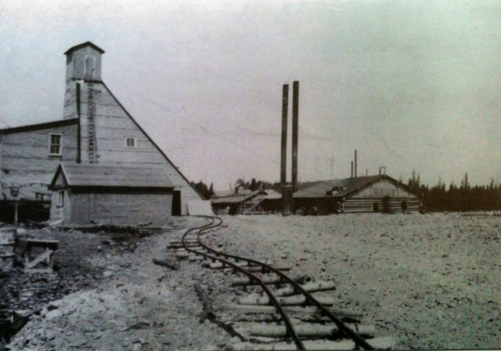 Black and white photograph of a mine headframe and a rudimentary building topped by two chimneys. In the foreground, a winding railway.