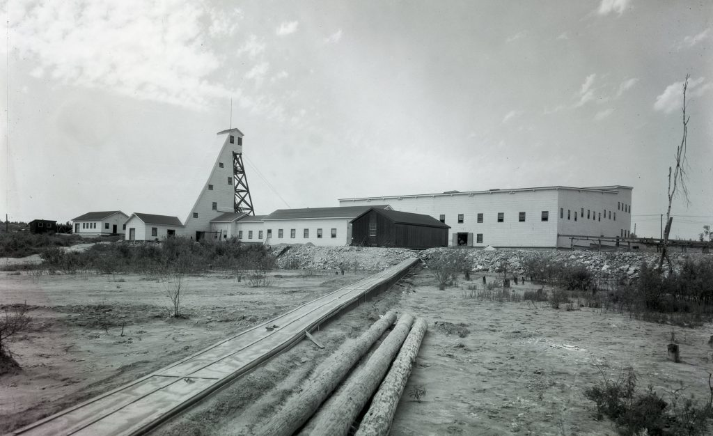 Black and white photograph of the infrastructures of Canadian Malartic Mines, including a headframe of planks. In the foreground, logs and a boardwalk provide access to the buildings.
