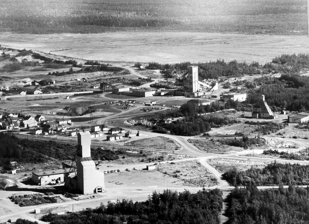 Black and white photograph of the installations of three mines, including their headframes, taken from a plane. In the centre, several houses of the private village of Halet. In the background, one of East Malartic's mine tailings sites.