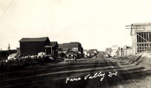Black and white photograph of a road lined with plank buildings on which walk several pedestrians. In the foreground, a taxi cab. At the bottom, an inscription in white: