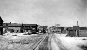 Photographie en noir et blanc d'une route en hiver bordée de bâtiments de planches ou en bois rond. Vu la circulation dans la neige, des roulières sont visibles au centre.