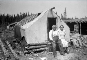 Black and white photograph of an elderly couple in front of a rudimentary dwelling: a wood and textile tent. Log cabins are visible on the right and in the background.