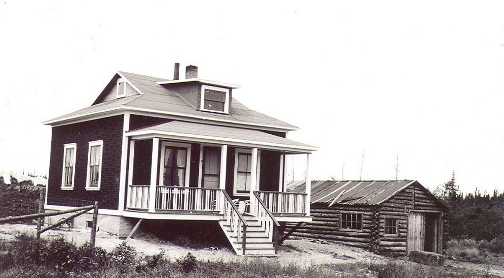 Black and white photograph of a clean, modern house with a front veranda. On the right, a rudimentary log garage.