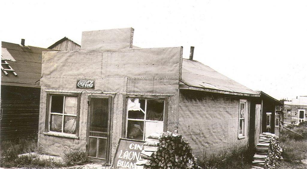 Photographie en noir et blanc d'une habitation en papier goudronné avec une façade de style Boomtown. Un enseigne est déposé au sol : « Gin LAUNDRY buanderie ».