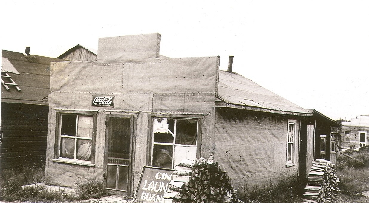"""Black and white photograph of a tar paper house with a Boomtown façade. A poster placed on the floor reads, """"Gin LAUNDRY buanderie""""."""