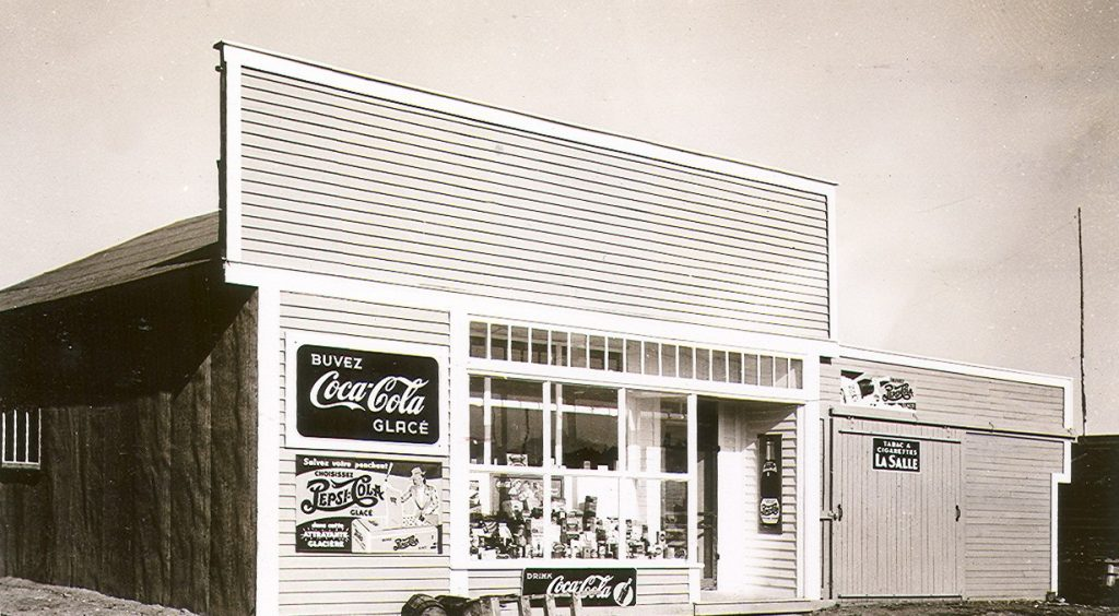 Black and white photograph of a plank house with a Boomtown façade on which several Coca-Cola advertisements are displayed. Several products are displayed in the window.