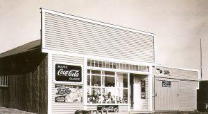 Photographie en noir et blanc d'une habitation de planches avec façade de style Boom-town sur laquelle plusieurs publicités « Coca Cola » sont affichées. Plusieurs produits sont présentés en vitrine.