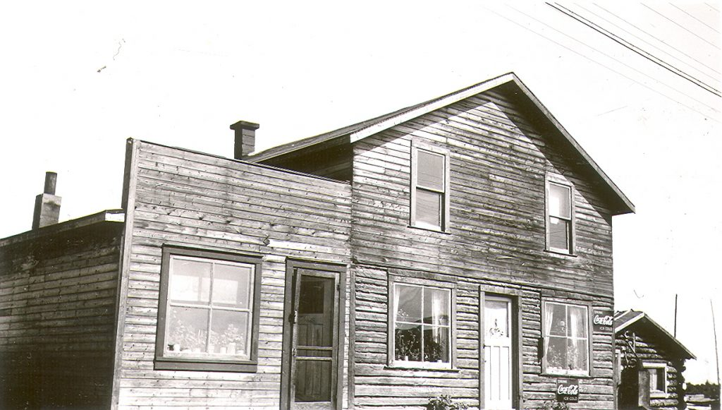 Black and white photograph of a plank building made up of two dwellings. Two Coca-Cola advertisements are displayed on the building. On the right, a log cabin.
