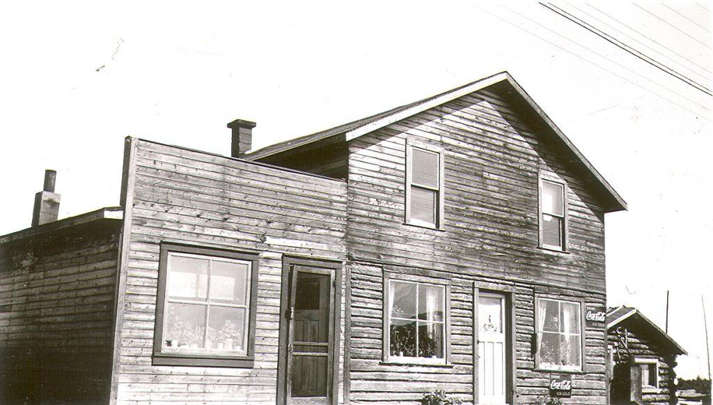 Photographie en noir et blanc d'un immeuble de planches contenant deux logements. Deux publicités de « Coca-Cola » sont affichées sur la résidence. À droite, une cabane en bois rond.