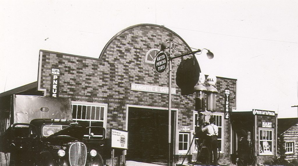 Black and white photograph of a garage with a tar paper front. Over the garage door, the