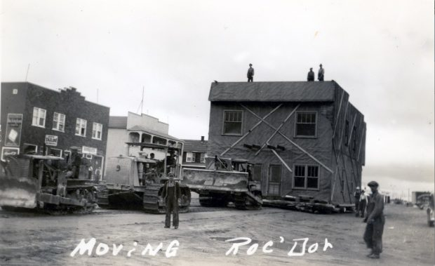 Black and white photograph of a two-storey building being moved by three tractors. Several men are on the roof. Several curious onlookers are at the scene. In the background, several buildings.