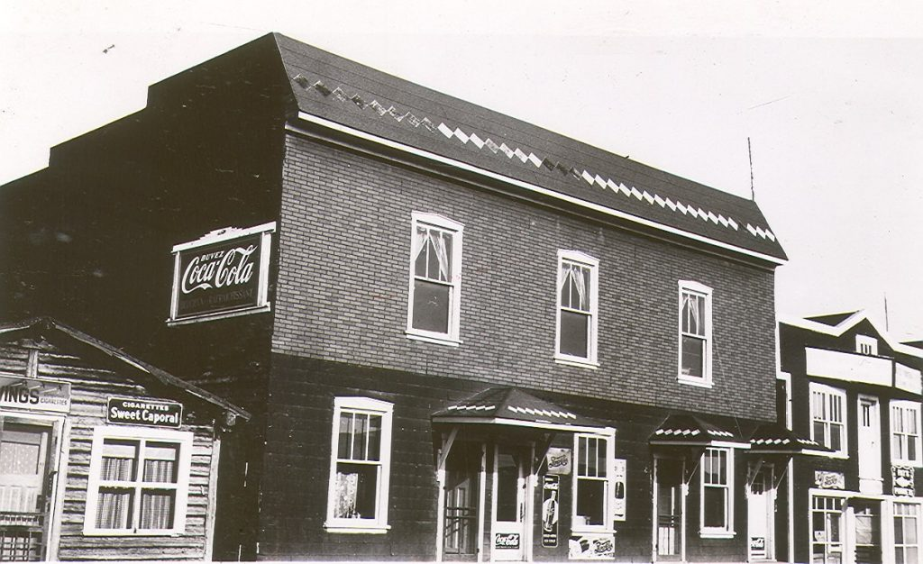 """Black and white photograph of a two-storey building covered with tar paper. The front has six windows and four doors. On the side, a """"Drink Coca-Cola"""" advertisement. On the right, the Frontenac Hotel. On the left, a log cabin."""