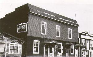 Photographie en noir et blanc d'un bâtiment de deux étages recouvert de papier goudronné. La devanture a six fenêtres et quatre portes. Sur le côté, une publicité « Buvez Coca-Cola ». À droite, l'hôtel Frontenac et une cabane en bois rond à gauche.