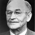 Black and white photograph of a man in a suit and tie wearing glasses and a thin moustache.