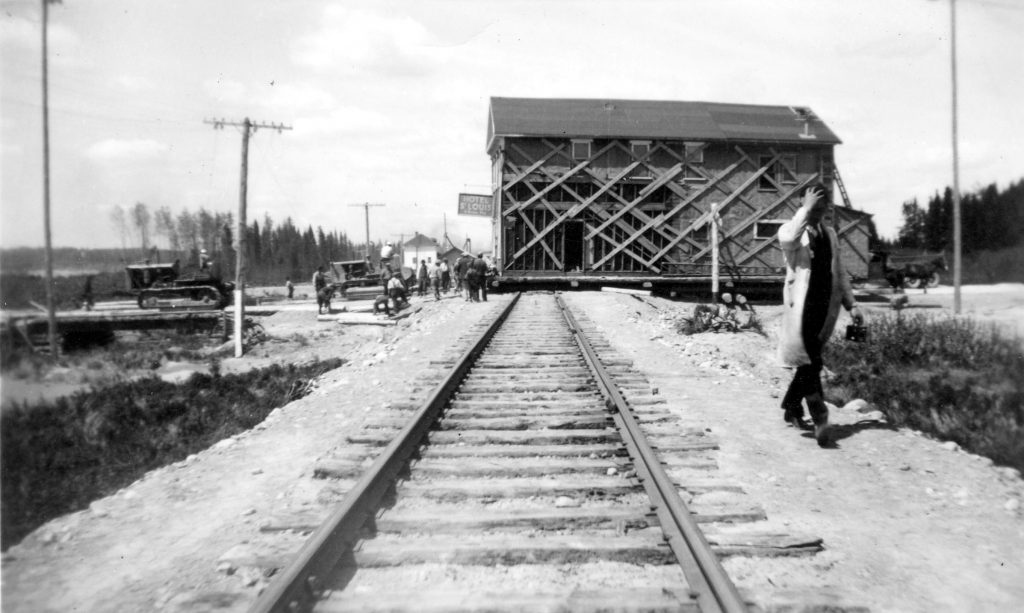 Black and white photograph of a two-storey building being moved across a railway. Hotel St-Louis' sign is visible. A dozen curious onlookers watch two tractors haul the building.