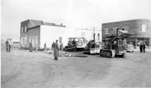 Black and white photograph of a two-storey building being pulled by three tractors. The logs used to roll the building are laid down in front. A person is on the roof. Several curious onlookers attend the scene.