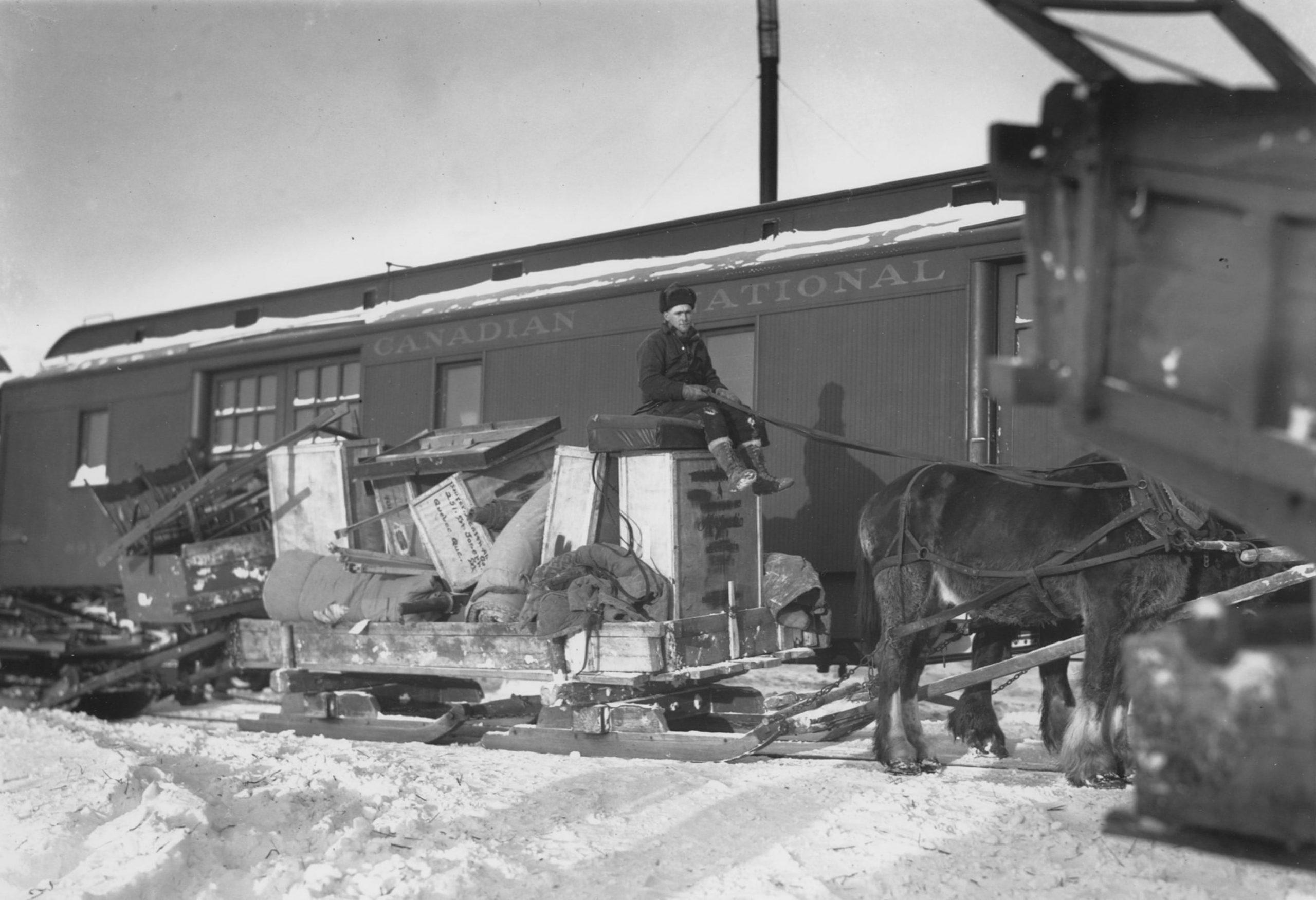 """Black and white photograph of a cart, filled to the brim with furniture and boxes, being pulled by two horses driven by a man sitting on the goods. Given the snow, the cart is on skis and the man is dressed warmly. A wagon bearing the inscription """"Canadian National"""" is in the background."""