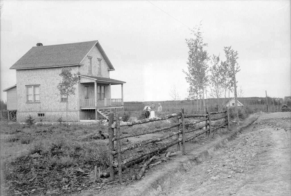 Black and white photograph of a two-storey house with three people posing in front of it. In the foreground, a fence. In the background, a small cluster of houses.