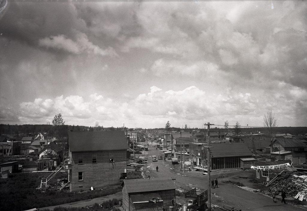 Photographie en noir et blanc d'une rue bordée des deux côtés de bâtiments rudimentaires. Des voitures et des piétons circulent au centre de la route non pavée qui est parsemée de trous d'eau.