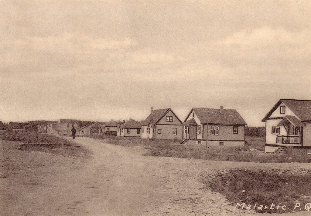 Sepia photograph of several residences lined up on one side of an unpaved street. In the centre, a man is walking. The inscription at the bottom right reads,