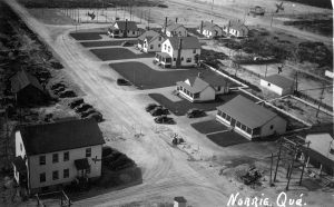 Black and white photograph of a hamlet consisting of several modern buildings. Several cars are parked in front of well-manicured lawns. Several sports fields (baseball, hockey, and tennis) are also visible.