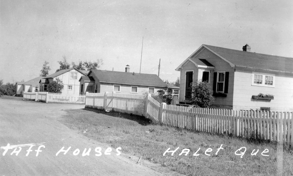 Black and white photograph of several plank houses surrounded by a white fence. At the bottom is the inscription