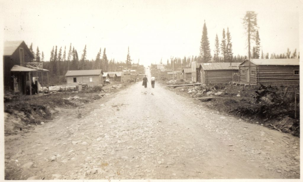 Sepia photograph of a gravel road lined with log cabins. In the centre, two men are walking towards a hill. Several conifers are visible in the background.