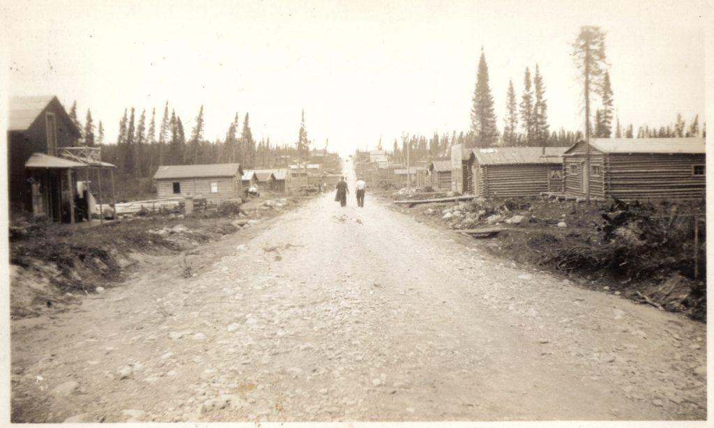 Photographie en sépia d'une route de gravier bordée de cabanes en bois rond. Au centre, deux hommes marchent vers une colline et plusieurs conifères sont visibles à l'arrière-plan.