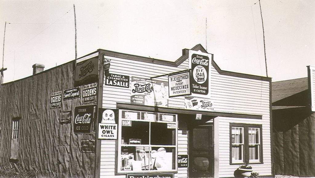 Black and white photograph of a building with a plank façade and tar paper side. A dozen advertisements are displayed, notably for Coca-Cola and various brands of cigarettes (Sweet Caporal and Lasalle).