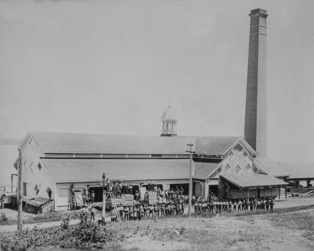 Mill employees pose for a group photo in front of lumber mill located beside a river.
