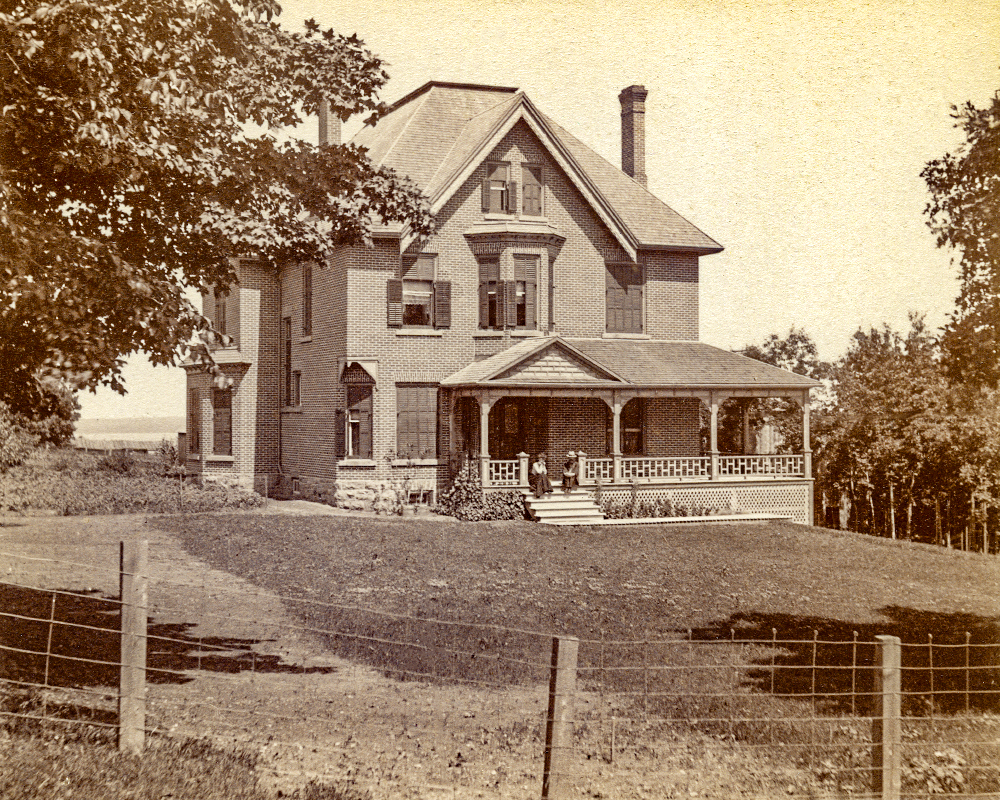 A young couple sits on the steps of a large, brick house with a wrap- around porch.