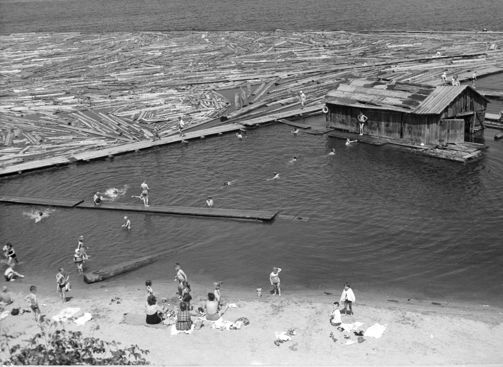 A group of women sit on a sandy beach watching children play and swim to a boat house is a short distance from the shoreline.