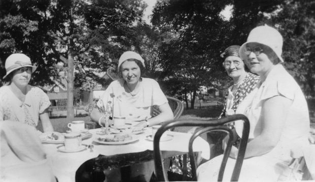 Four ladies wearing hats pose for the camera as they sit outdoors at a table set for a tea party.