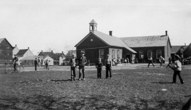 Children play in front of a brick school building equipped with a small bell tower.