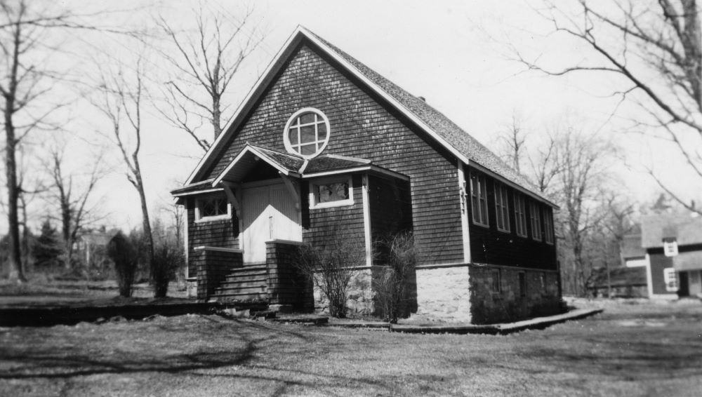 A peaked roof covers the entrance to a small church covered in cedar shingles.