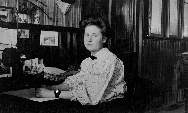 A young woman sits at her desk in an office lined with wooden panels.