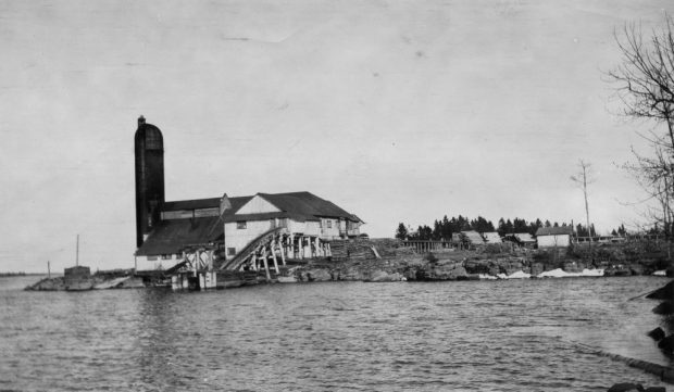 A mill on a rocky shoreline is surrounded by piles of cedar shingles and cut railway ties.