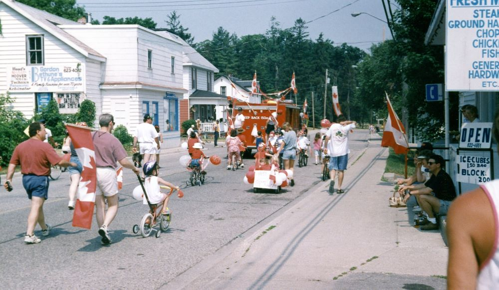 A decorated fire truck leads a parade of children riding bicycles and adults carrying Canadian flags.